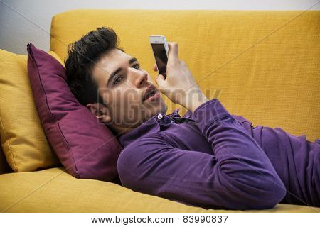 Attractive young man recording voice message on cell phone