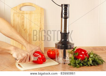 Hands chefs cut red bellpepper on kitchen table