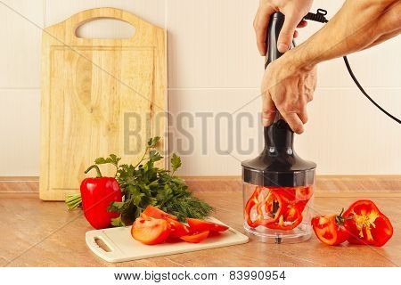 Hands cooks are going to chop red pepper in blender