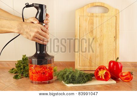 Hands chefs mixed red pepper and tomato in blender