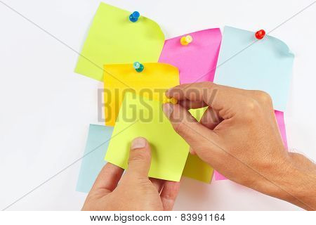 Hand attaches green sticker on white message board