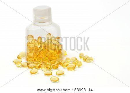 Vitamin Capsules With  E Poured Out Of Bottle