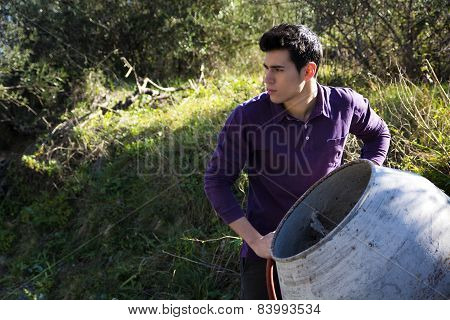 Young man working with a cement mixer