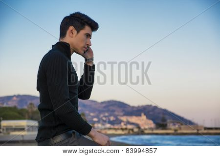 Young man at the seaside talking on cell phone