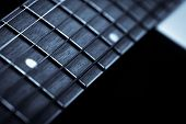 stock photo of fret  - Detail of the fret board of an acoustic guitar on a dark background - JPG