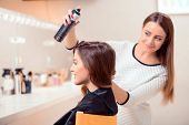 foto of brown-haired  - Side view of a young beautiful woman sitting in hair salon and looking into the mirror while her hairdresser getting her hair done with hair spray - JPG
