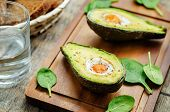 stock photo of continental food  - avocado baked with egg on a dark wood background - JPG