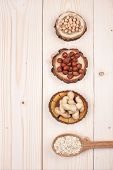 picture of oats  - Overhead view of different types of nuts and oats in wooden spoons  on wooden table with place for text - JPG