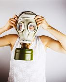 foto of rubber mask  - Woman holding gas mask up to her head - JPG