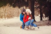 image of sled  - happy couple riding a sled in the winter forest - JPG