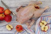 stock photo of crude  - Crude hen and apples process of preparation of a stuffed hen with apples - JPG