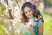 foto of magnolia  - Portrait of beautiful young girl in the bushes magnolia - JPG