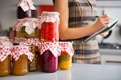 image of pickled vegetables  - Closeup on jars with homemade fruits jam and pickled vegetables and housewife writing in notepad in background - JPG