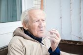 pic of exhale  - thoughtful old man with a cigarette he is exhaling smoke - JPG