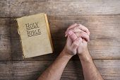 image of praying hands  - Hands of praying young man and Bible on a wooden desk background - JPG