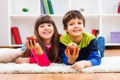 image of little boys only  - Cute little girl and little boy are holding apple and looking at camera - JPG