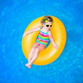 pic of rings  - Cute funny little toddler girl in a colorful swimming suit and sun glasses relaxing on an inflatable toy ring floating in a pool having fun during summer vacation in a tropical resort - JPG