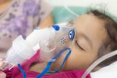 stock photo of exhale  - The girl is being cured lung infection with aerosols inhalation - JPG