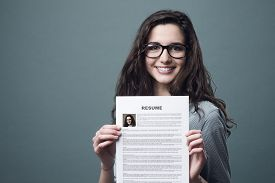 foto of candid  - Young smiling cheerful woman holding her resume - JPG