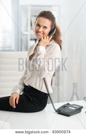 Smiling Woman Sitting On Desk And Talking On The Telephone