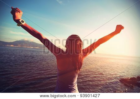 young woman open arms at sunrise seaside