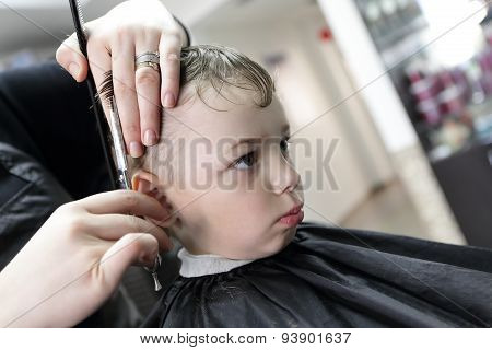 Barber Cutting Hair Of A Serious Boy