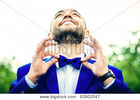 Man With Beard Holding His Bow Tie By Fingers