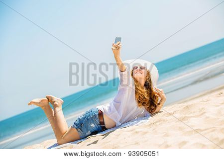 Beautifil young woman lying on the beach at sunny day and taking selfie with phone