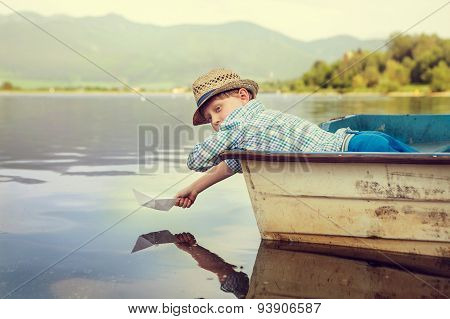 Little Boy Launch Paper Ship Lying In Old Boat