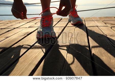 healthy lifestyle sports woman tying shoelace on wooden boardwalk sunrise seaside