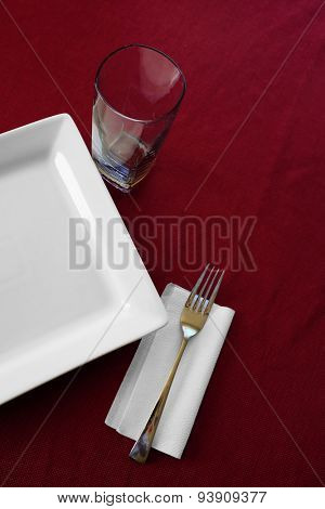 Detail of table place setting with plate cup fork and red table cloth