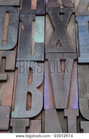 antique wood letterpress printing blocks with color ink patina, random collection with L, X, V, and B letters