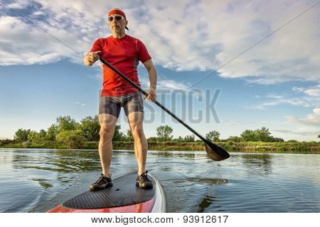 senior muscular male paddler enjoying paddling on stand up paddleboard, calm lake in summer scenery