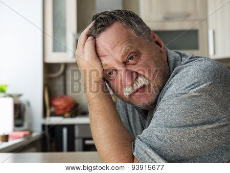 Mature tired man sitting at a table in his apartment