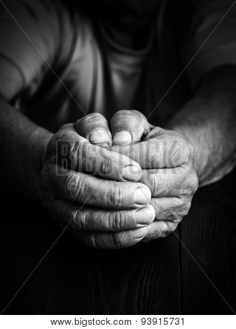 Wrinkled hands elderly man at table. Black and white photo