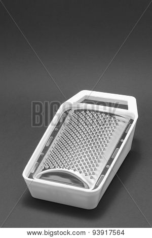 Grater With White Plastic Lining On A Black Background