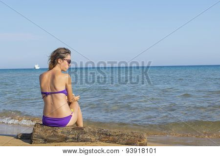 Young Girl Sitting Alone At The Beach