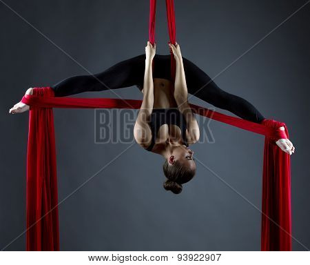 Sexy female acrobat performs hanging upside down
