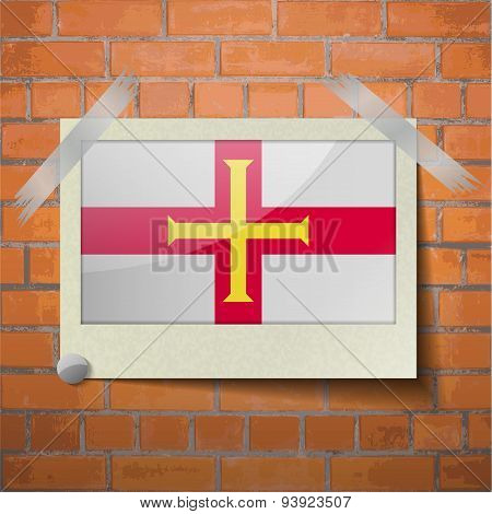 Flags Guernsey Scotch Taped To A Red Brick Wall