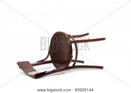 Studio shot of a mahogany brown wooden chair fallen down on the floor isolated on white background