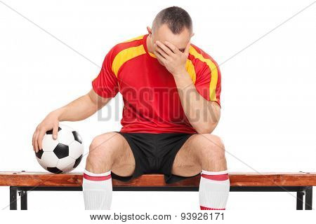 Worried football player sitting on a wooden bench, holding a ball and hiding his face with one hand isolated on white