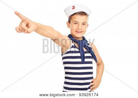 Studio shot of a little male kid in a sailor costume pointing forward with his hand and looking at the camera isolated on white background