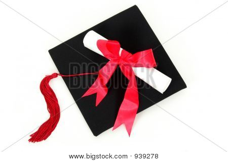 Diploma Resting On Graduation Cap