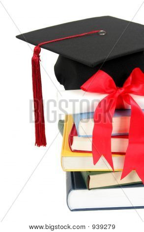 Graduation Cap And Diploma On Top Of Stack Of Books
