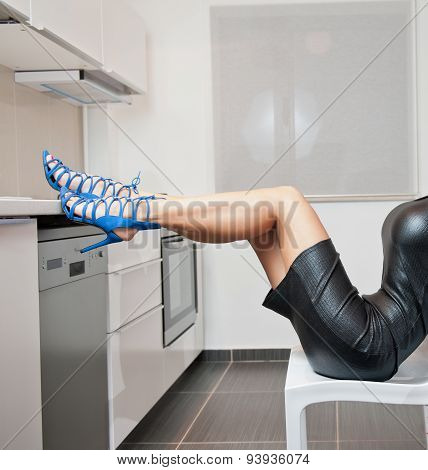 Perfect body woman in short tight fit leather dress and blue shoes posing relaxed in modern kitchen