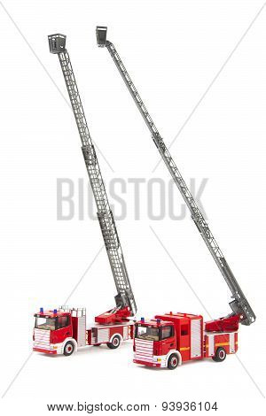 Two Toy Firetrucks Wit Ladders Extended On White Background