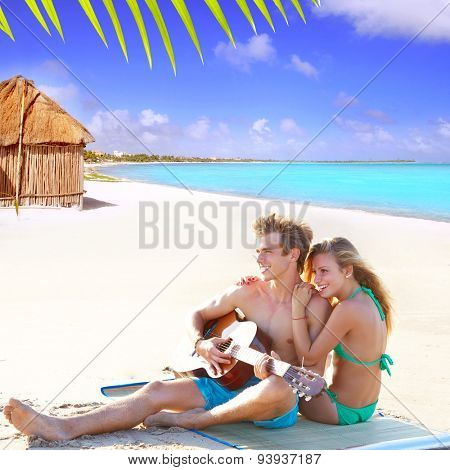 Blond couple sitting in the Cancun beach sand playing guitar photo mount