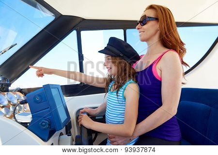 Kid girl pretending be a captain sailor cap with her mother in boat indoor
