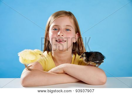 Kid girl with chicks playing on table with blue background