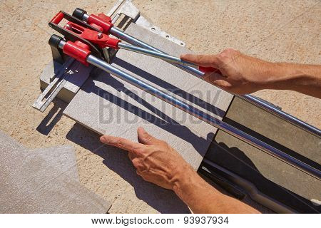 tile cutter machine with mason hands cutting tiles